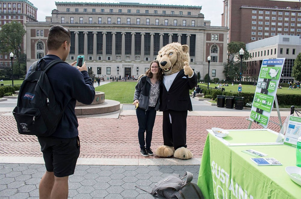 Student taking photo with Roar-ee with Low Library in background
