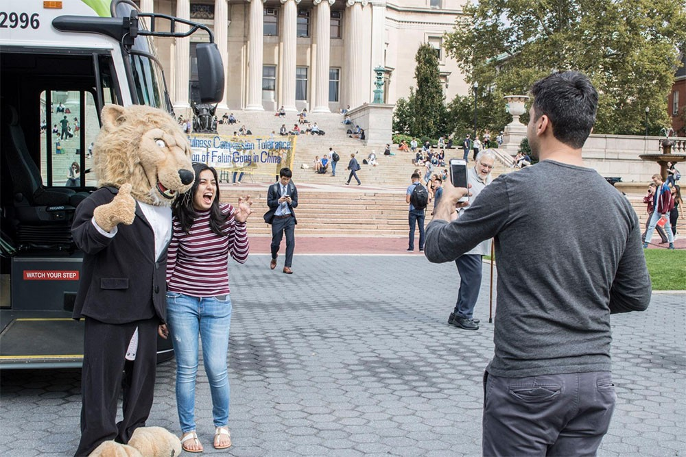 Student poses with Roar-ee in front of electric bus