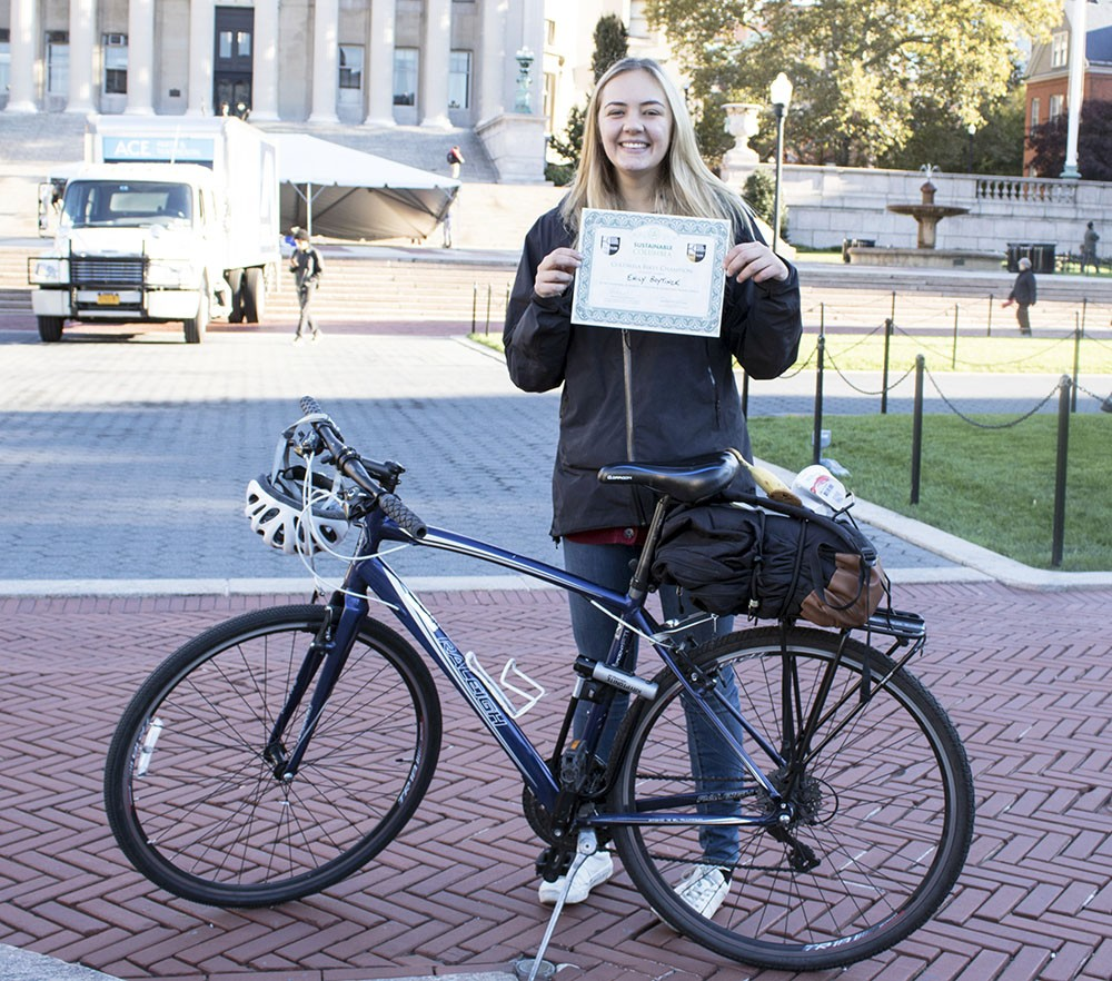 Emily Boytinck poses with her bike and her Sustainable Commuter award at the 2018 Bike Recognition Breakfast on College Walk